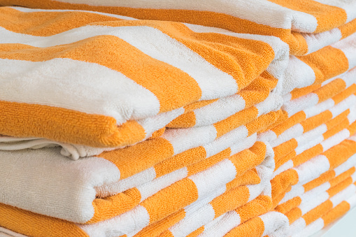 1131900491 istock photo Bath towel rolls fabric texture cloth background in white orange stripe for swimming pool, sea beach, gym fitness in resort hotel 1130377273