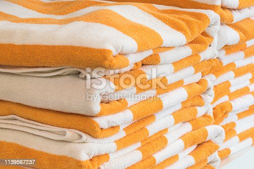1131900491istockphoto Bath towel rolls fabric texture cloth background in white orange stripe for swimming pool, sea beach, gym fitness in resort hotel 1139567237