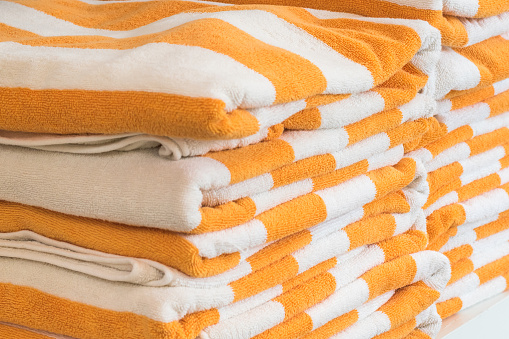 1131900491 istock photo Bath towel rolls fabric texture cloth background in white orange stripe for swimming pool, sea beach, gym fitness in resort hotel 1139567237