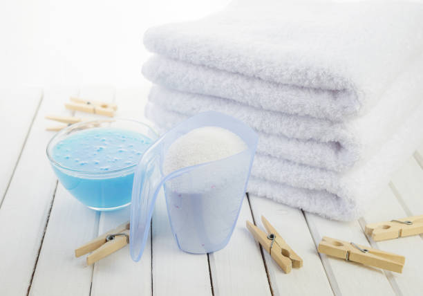 Bath towels, washing powder, fabric softener and wooden clothespins stock photo