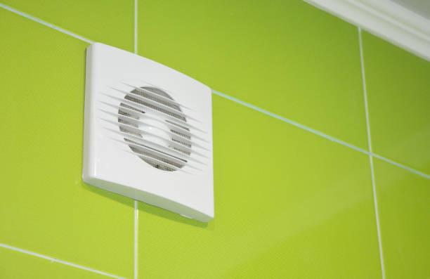 Bad vent fan met groene tegels muur. Witte badkamer ventilatiesysteem. foto