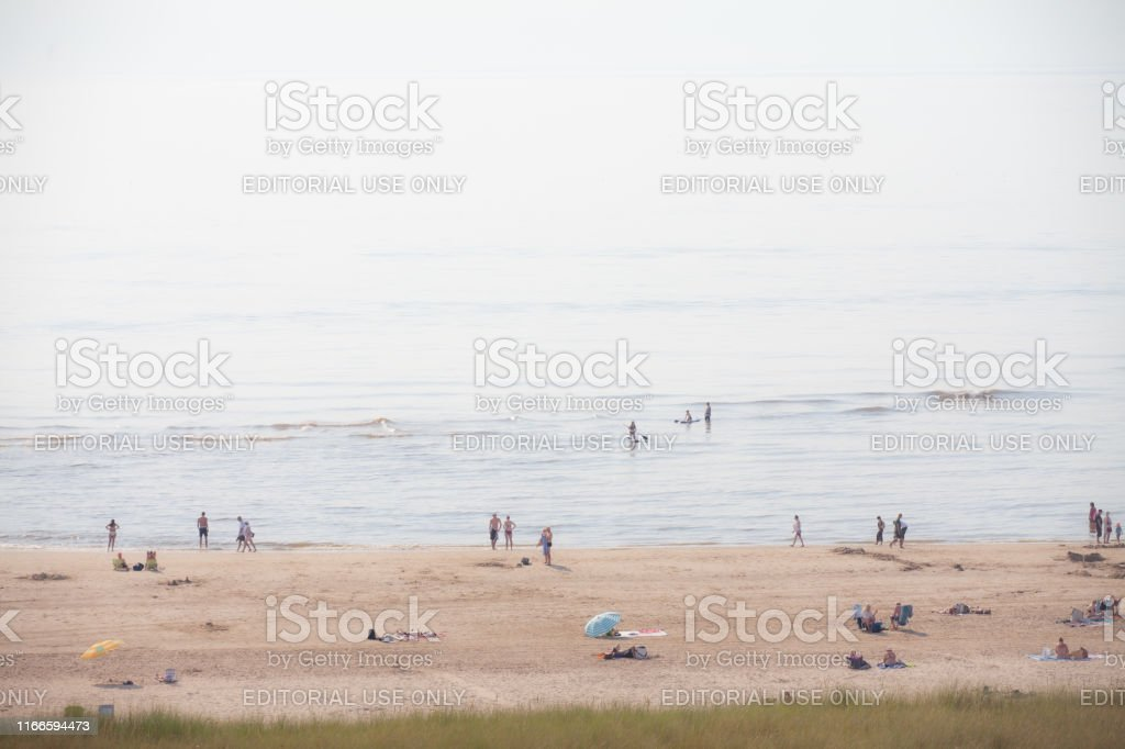bathing people on the beach in the glistening sun (high key exposure) Egmond aan Zee, Netherlands - June 24, 2019: bathing people on the beach in the glistening sun (high key exposure) Beach Stock Photo