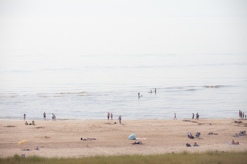 Bathing People On The Beach In The Glistening Sun Stock Photo - Download Image Now