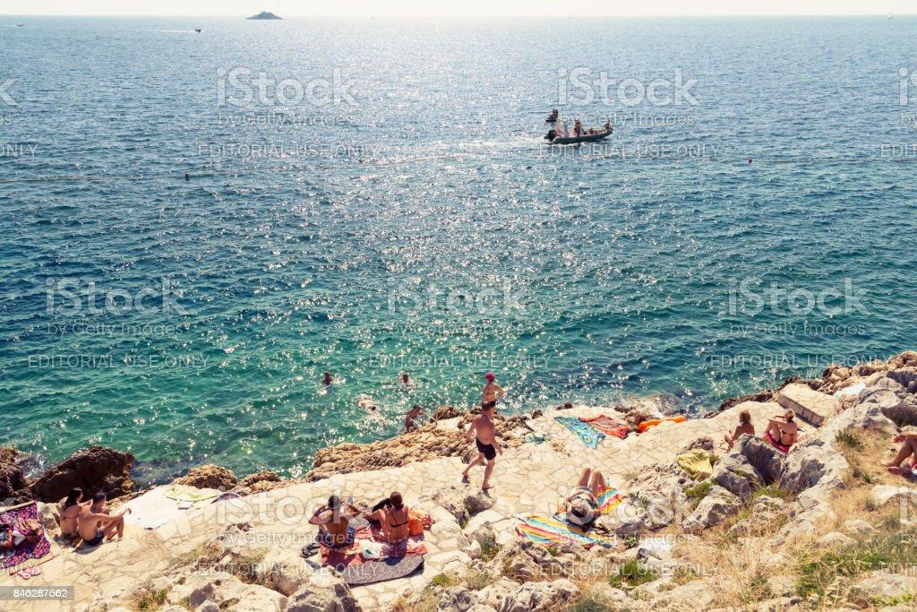 Bathing people on the beach of Rovinj, Croatia stock photo