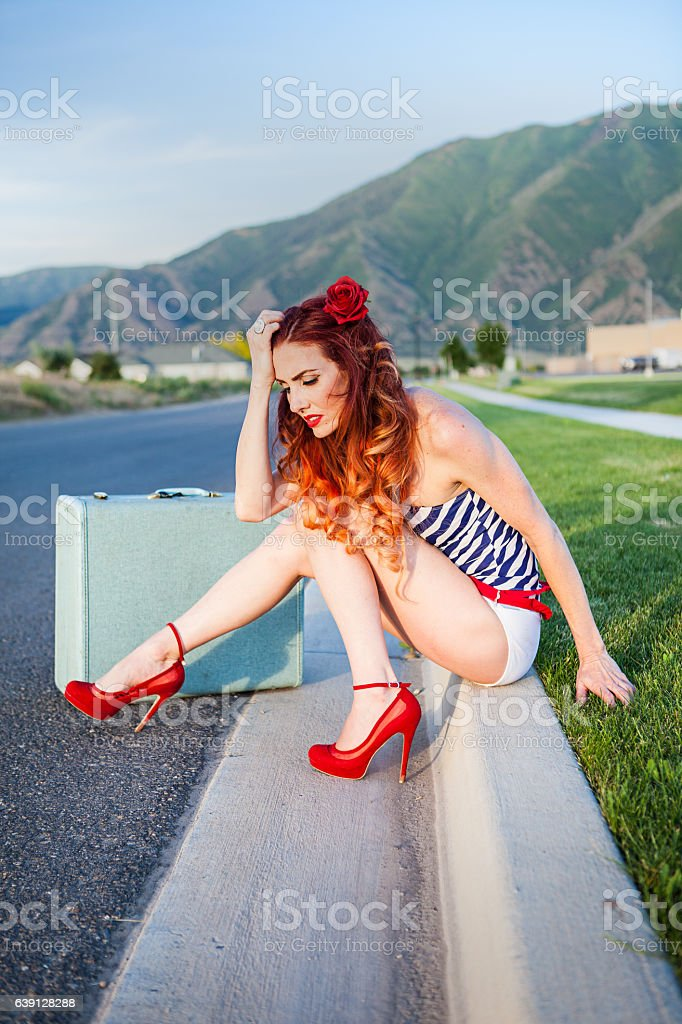 Bathing Suit Hitch Hiker sitting by a road stock photo