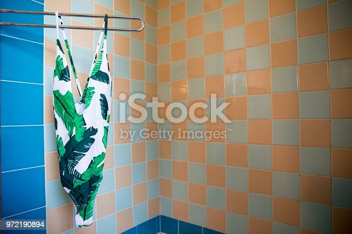 One piece bathing suit hanging up in a bathroom