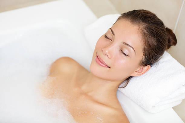 Mulher de banho relaxante na banheira - foto de acervo