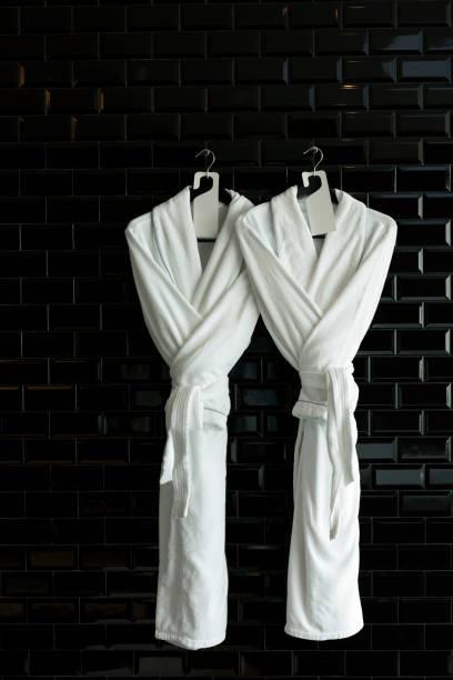bathrobe for couple hang on black wall - accappatoio foto e immagini stock