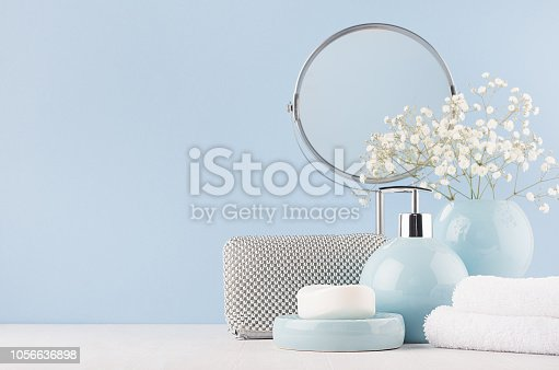 1056636898 istock photo Bathroom decor for female in light soft blue color - circle mirror, silver cosmrtic bag, white flowers, towel, soap and ceramic smooth vase on white wood table. 1056636898