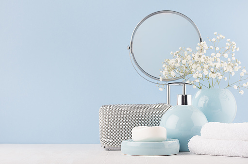 istock Bathroom decor for female in light soft blue color - circle mirror, silver cosmrtic bag, white flowers, towel, soap and ceramic smooth vase on white wood table. 1056636898