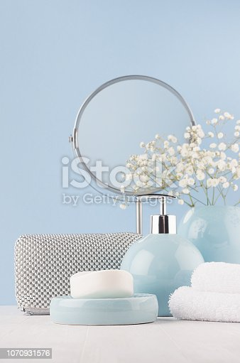 1056636898 istock photo Bathroom decor for female in light soft blue color - circle mirror, silver cosmrtic bag, white flowers, towel, soap and ceramic smooth vase on white wood table, vertical. 1070931576