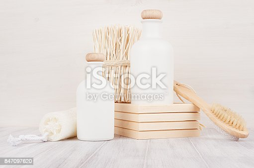 847096968 istock photo Bathroom decoration. Blank white cosmetics bottles with shower puff, twigs on white wood board, mock up. 847097620