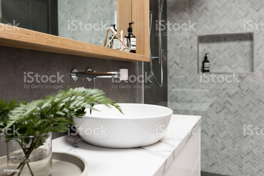 Bathroom details clean white basin with shower tiling behind stock photo