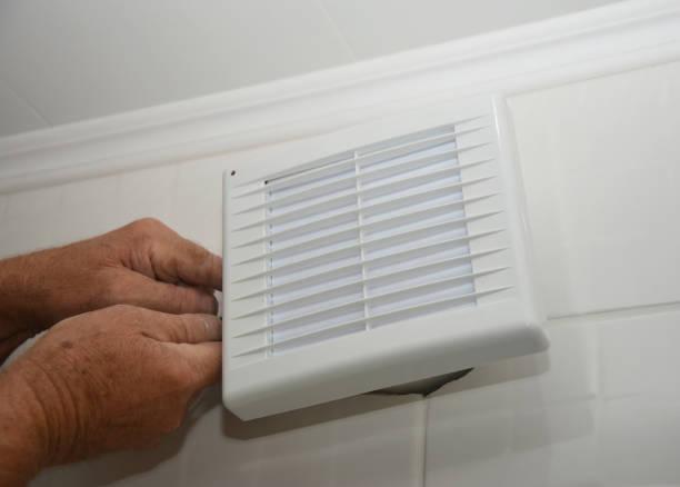 Badkamer afzuigkap, uitlaatventilator reparatie, installatie. Klusjesman installeert nieuwe badkamer vent ventilator, ventilatiesysteem in het huis badkamer foto