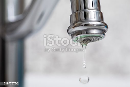 Close-up of faucet with turned drop water in modern bathroom.