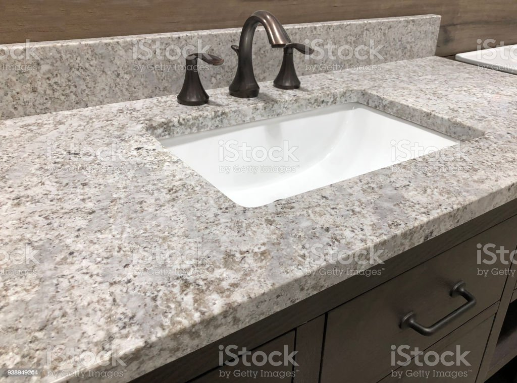bathroom granite counter over wooden vanity cabinet and white rectangular sink with chrome faucet stock photo
