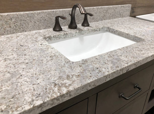 bathroom granite counter over wooden vanity cabinet and white rectangular sink with chrome faucet bathroom granite counter over wooden vanity cabinet and white rectangular sink with chrome faucet quartz stock pictures, royalty-free photos & images