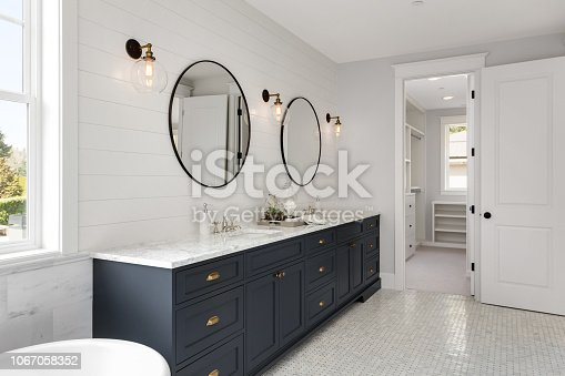 istock Bathroom in New Luxury Home with Two Sinks and Dark Blue Cabinets. Shows Walk-In Closet 1067058352