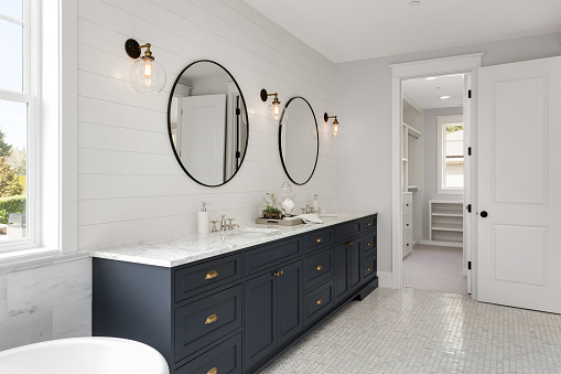 Bathroom in New Luxury Home with Two Sinks and Dark Blue Cabinets. Shows Walk-In Closet