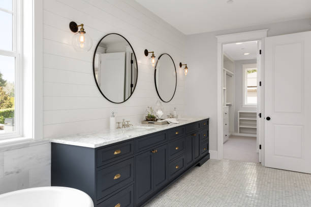 Bathroom in New Luxury Home with Two Sinks and Dark Blue Cabinets. Shows Walk-In Closet master bathroom in new home model home stock pictures, royalty-free photos & images