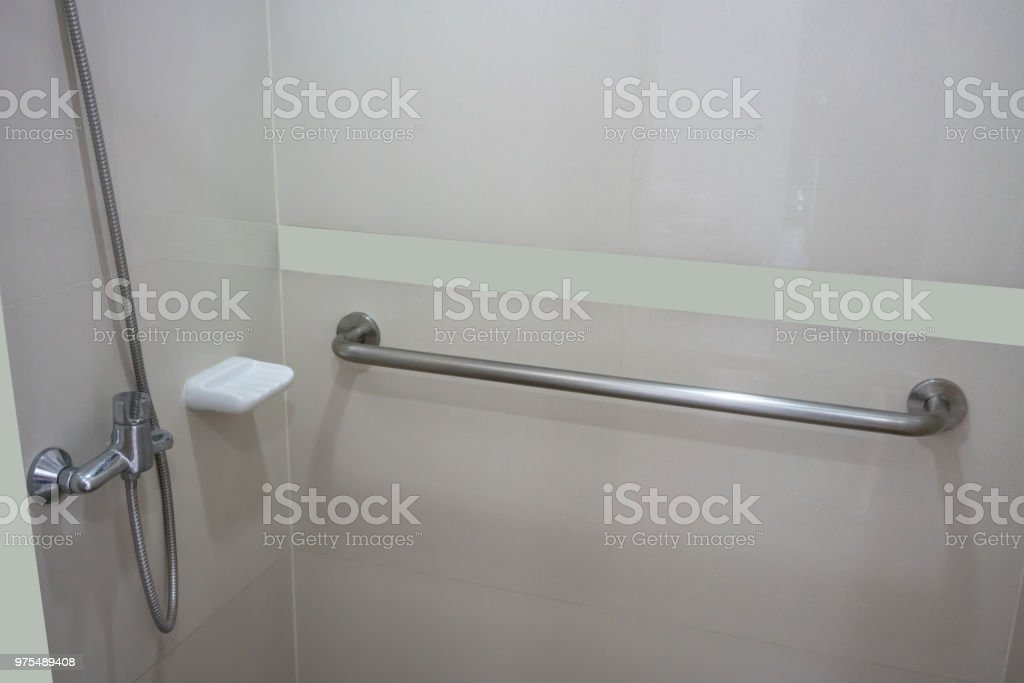 Bathroom interior in patient room with basic required equipment. Modern design in beige color. stock photo