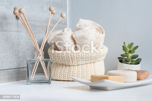 Modern bathroom interior comprising a cotton basket full of small towels, natural soap and perfume bottle with wooden diffuser