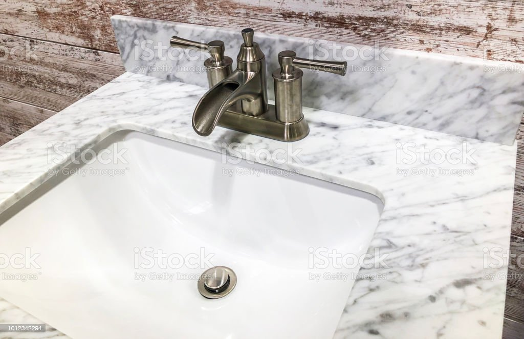 Bathroom Marble Countertop With White Sink Chrome Faucet And White Cabinets Stock Photo Download Image Now Istock