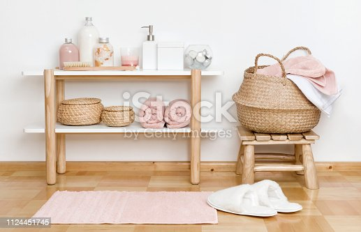 Bathroom partial interior with wooden shelf, stool and spa products