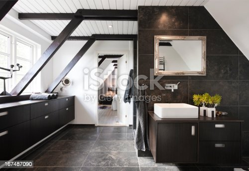 Bathroom in conjunction with bedroom. Structural beams, dark wood and granite tiles.