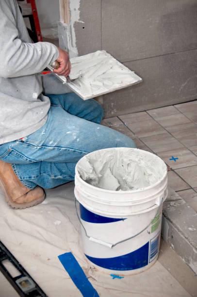 badezimmer renovierung: auftragnehmer putting mortar auf fliesen - fliesenkleber stock-fotos und bilder