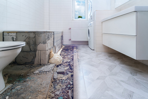 Bathroom renovation before and after. Laying new stone tiles in modern math room. Comparison view of floor reconstruction
