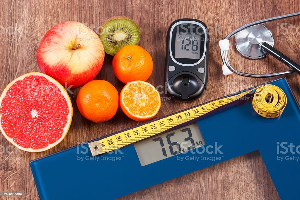 Bathroom scale and glucometer, centimeter, stethoscope and healthy food stock photo