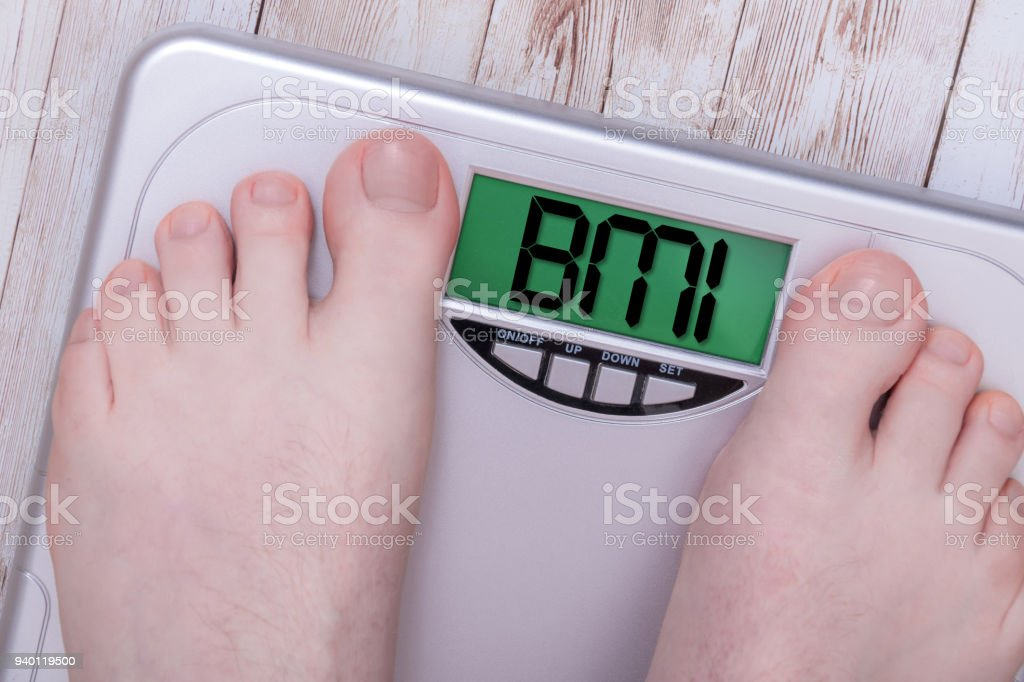 Bathroom scales on wooden floor with LCD screen saying BMI – zdjęcie