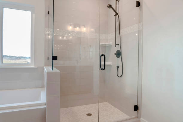 Bathroom shower stall with half glass enclosure adjacent to built in bathtub stock photo