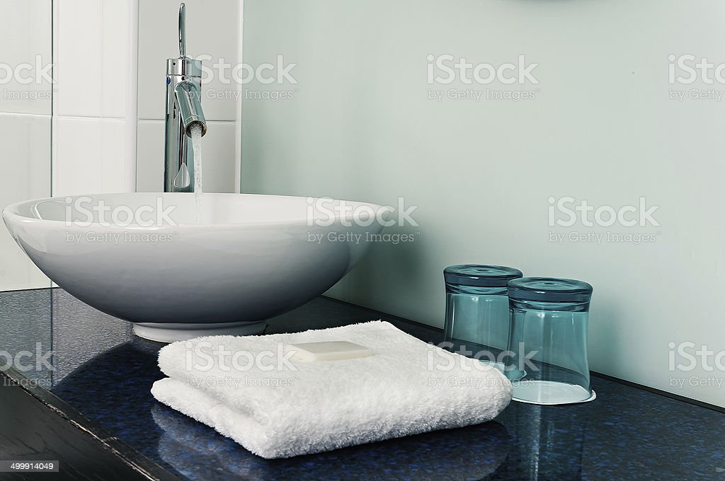 Bathroom sink counter towels water glass blue stock photo