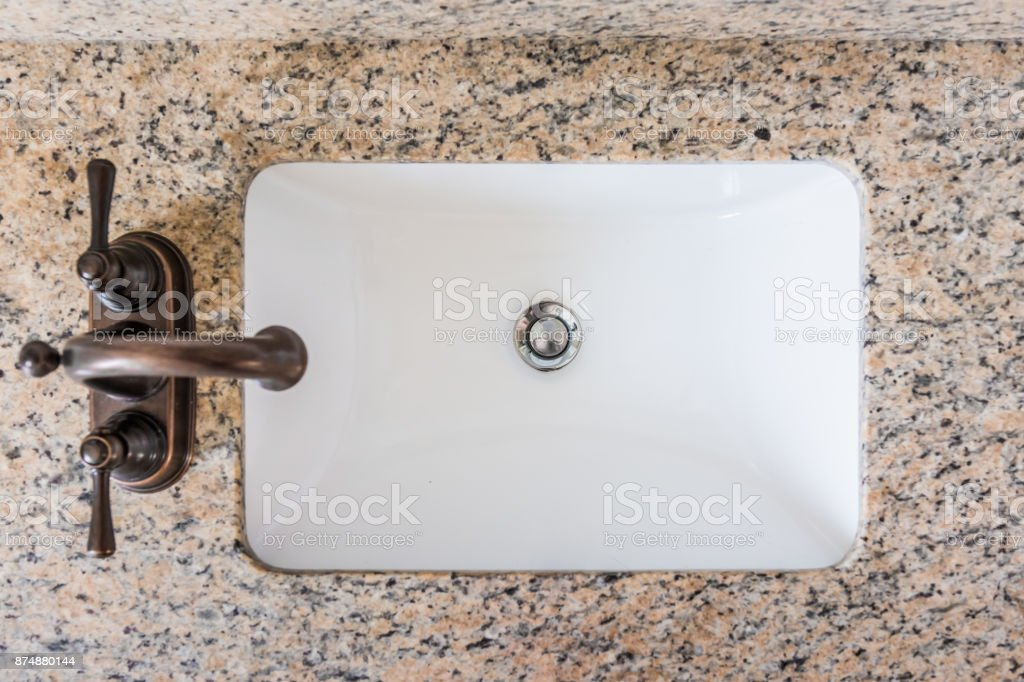 Bathroom sink, Granite counter, bronze faucet and white beadboard or wainscoting stock photo