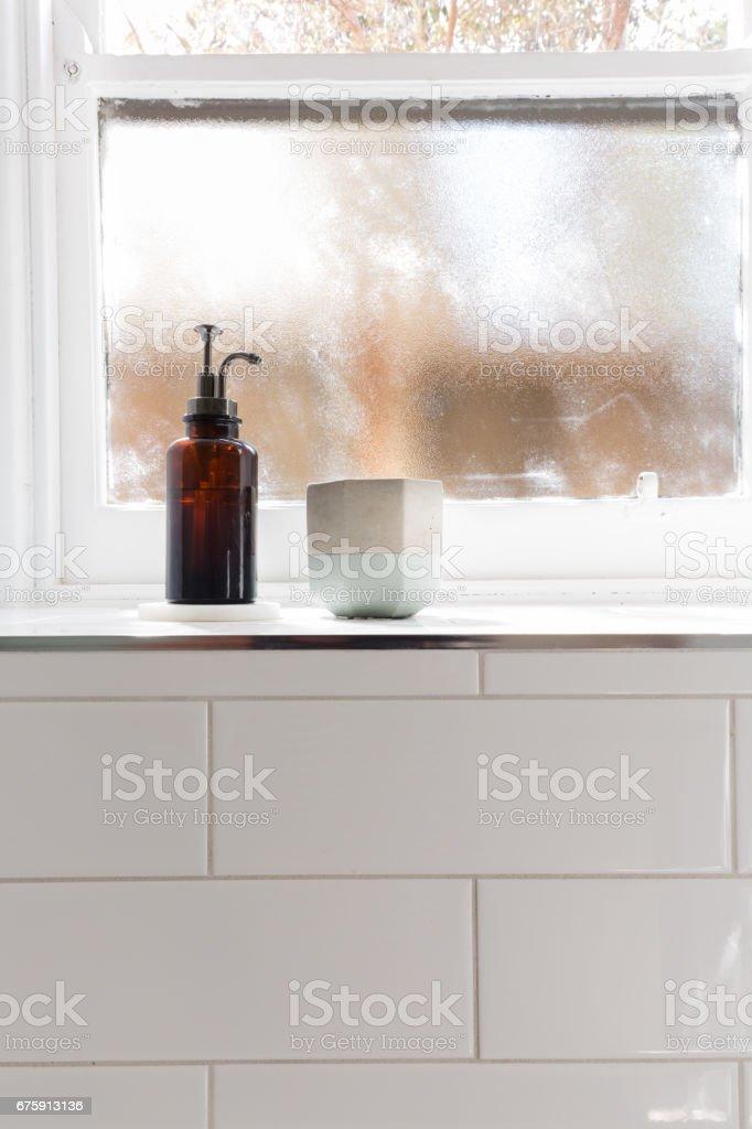 Bathroom soap dispenser and pot on window ledge stock photo