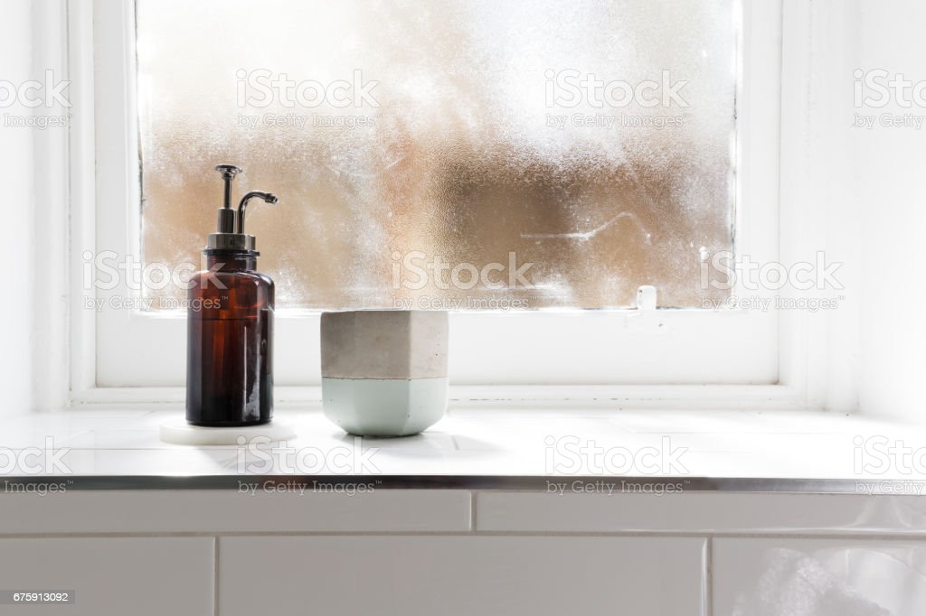 Bathroom soap dispenser and pot on window ledge with background stock photo