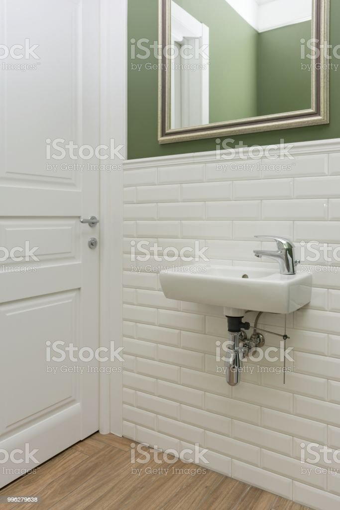 Picture of: Bathroom Toilet Room Interior Closeup The Walls Are Painted Green Covered With Decorative Ceramic Tiles With White Glossy Bricks Stock Photo Download Image Now Istock