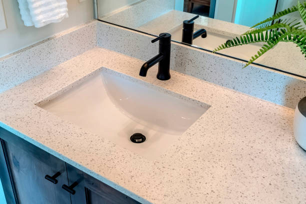 Bathroom white countertop with single basin undermount sink and black faucet stock photo
