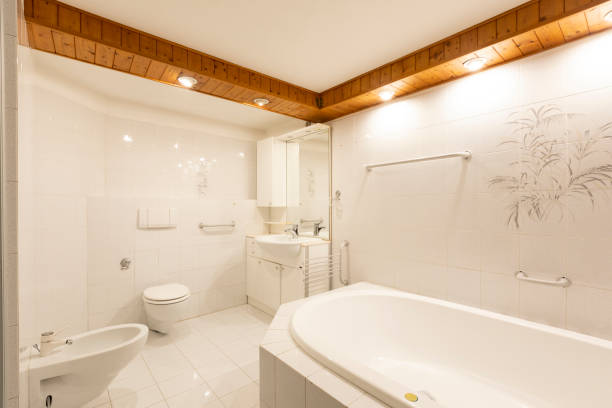 Badezimmer mit weißen Fliesen und Holzdecke – Foto