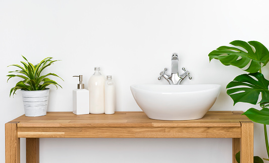 istock Bathroom wooden table with washbasin, faucet, plants and soap bottles 1060907816