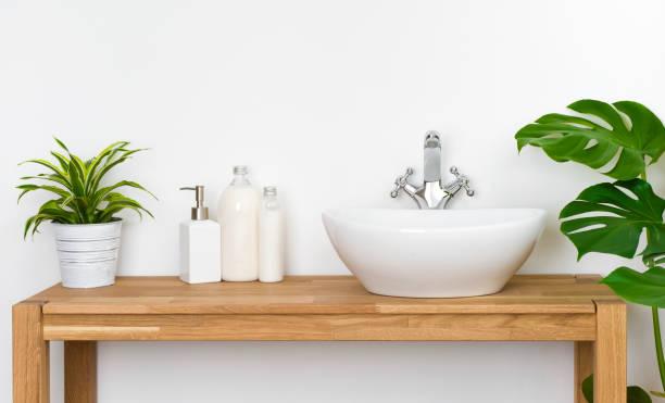 욕실 세 면 대, 수도 꼭지, 식물 및 soap 병 나무 테이블 - 욕실 뉴스 사진 이미지
