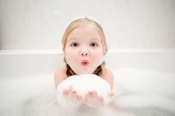 Bathtime bubbles A cute little girl having fun in a bath full of bubbles! bubble bath stock pictures, royalty-free photos & images
