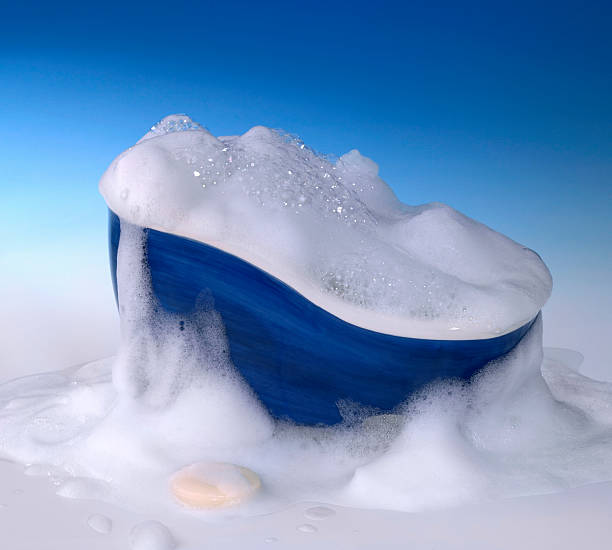 bathtub and foam symbolic cleaning and washing background with bathtub,soap and lots of foam in blue gradient back bubble bath stock pictures, royalty-free photos & images