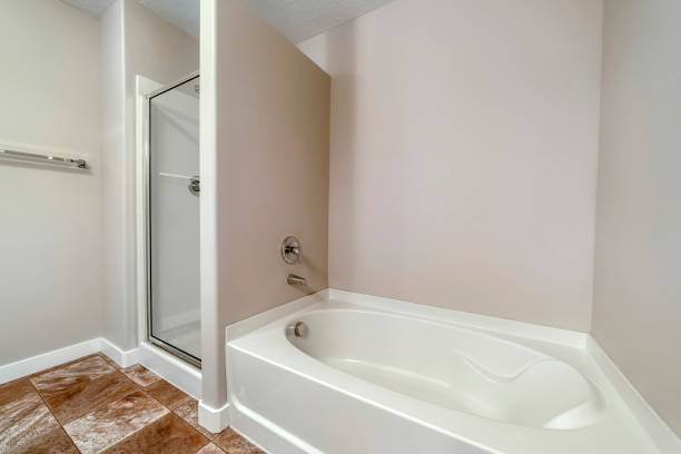 Bathtub and shower stall with glass door inside bathroom with tiles on floor stock photo