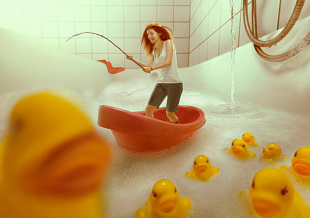 Bathtub Fishing Redhead girl fishing in the bath tub lake. kids cleaning up toys stock pictures, royalty-free photos & images