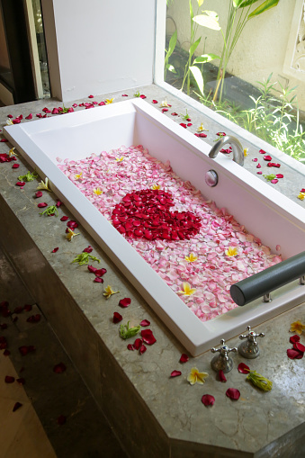 A bathtub full of roses and frangipani petals, spa weekend, wellbeing, body care and beauty concept