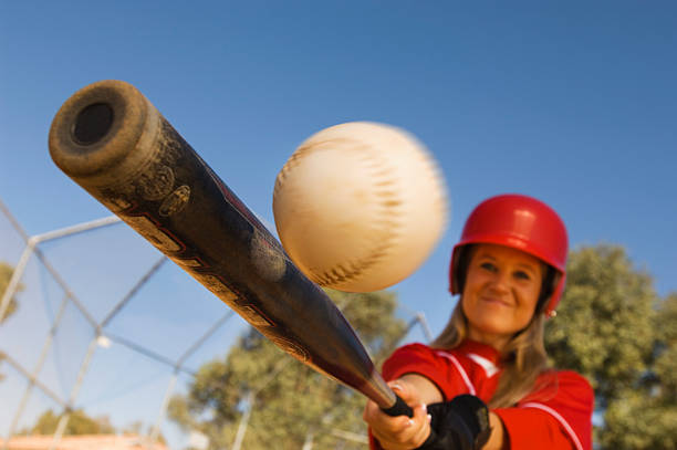 batter hitting softball - softball stock photos and pictures