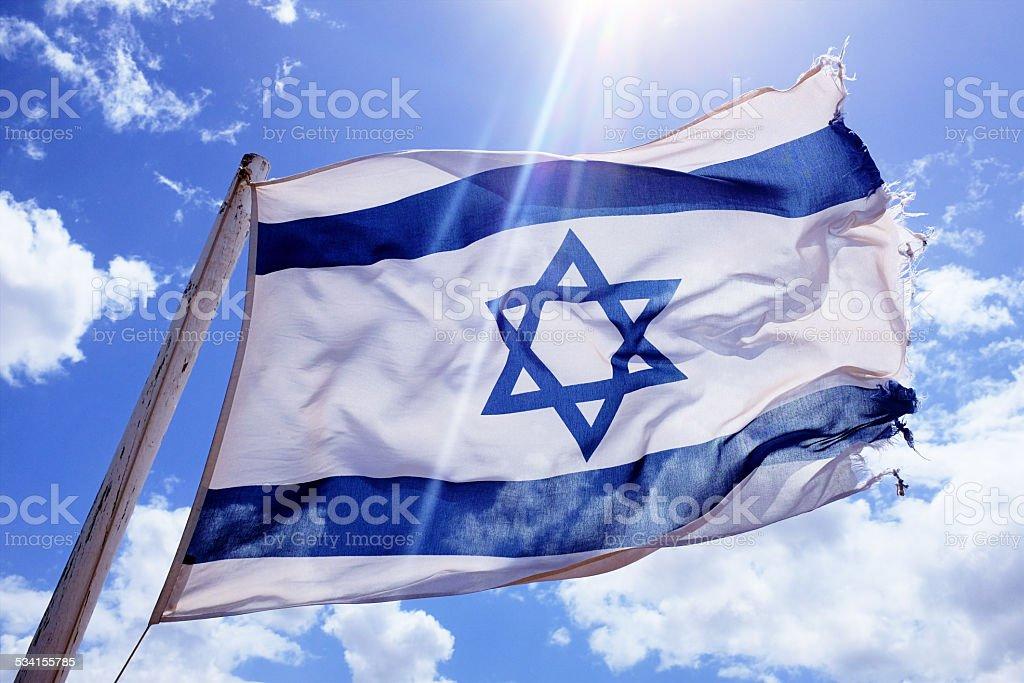 Battered and frayed Israeli national flag flying bravely in wind stock photo